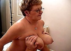 A granny with big tits rides on top of a cock
