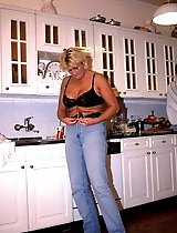 Hot MILF shows a little striptease for a teen stud in the kitchen